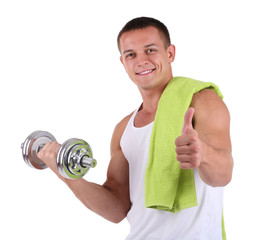 Young muscular sportsman with dumbbell and towel isolated