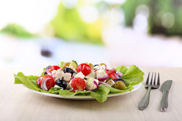 Greek salad in plate on wooden table on natural background