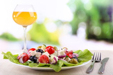 Greek salad in plate and glass of wine