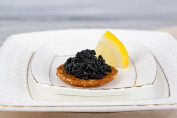 Black caviar on crispy bread on plate