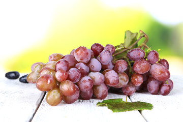 Bunch of ripe grape on wooden table on natural background