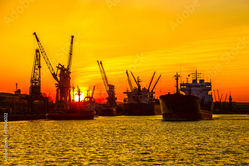 Silhouette of sea port cranes over sunset