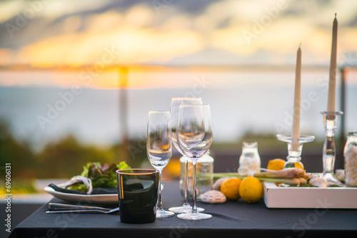 Leinwanddruck Bild Empty glasses set in restaurant  Dinner table outdoors at sunset