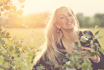 Beautiful blonde woman in the park at sunset