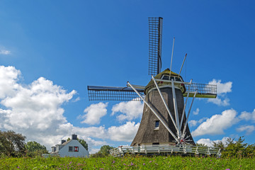 Windmill on a dike under a blue sky