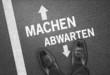 """Mann steht auf der Straße """"Machen / Abwarten"""""""