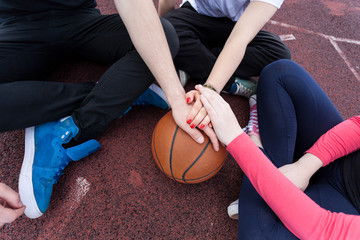 Friends holding hands on basketball