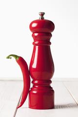 Rote Peperoni, rote Pfeffermühle auf weissem Holztisch
