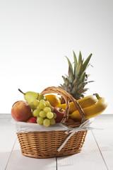 Obstkorb mit Früchte, weisser Holzuntergrund