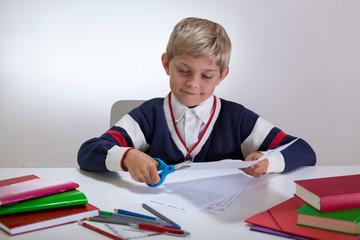 Boy using scissors on the desk
