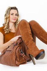 portrait of sitting woman wearing brown clothes and boots with a
