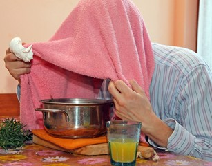 man with towel breathe balsam vapors to treat colds and the flu