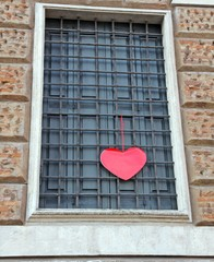 red heart hanging on the grating outside a building