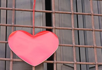 red heart hanging on the grid of a window