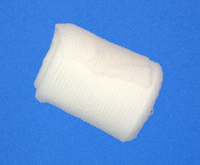 Roll of first aid gauze bandage on a blue background
