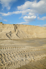 Sand quarry, heap of sand with tire tracks, landscape