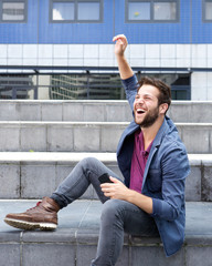 Cheerful young man holding mobile phone