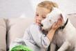 canvas print picture - Junges Mädchen umarmt ihren Hund auf Sofa