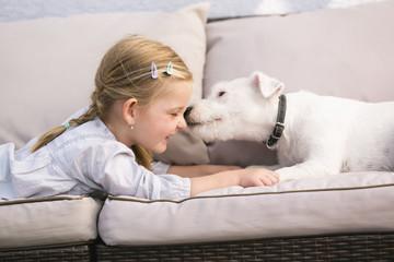 Junges Mädchen liegt mit ihrem Hund auf Sofa