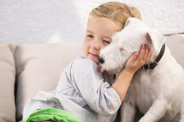 Junges Mädchen umarmt ihren Hund auf Sofa