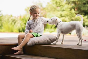 Junges Mädchen sitzt draußen auf Holztreppe mit ihrem Hund