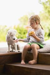 Mädchen sitzt draußen auf Holztreppe mit Hund