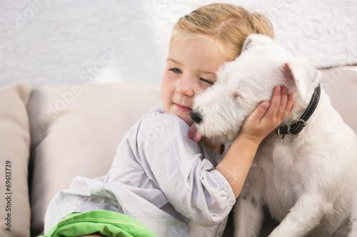 canvas print picture Junges Mädchen umarmt ihren Hund auf Sofa