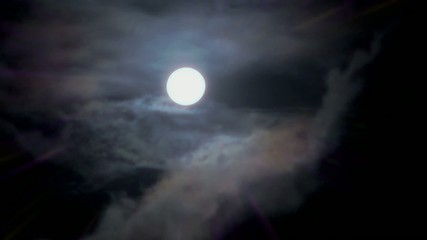 Magic full moon and white clouds on nightly sky