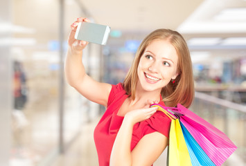 Selfie, a successful shopping happy woman with shopping bags