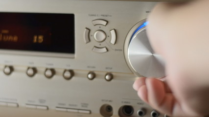 Hand turns volume on receiver