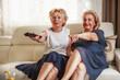 Zdjęcia na płótnie, fototapety, obrazy : Senior women watching television on sofa, in living room