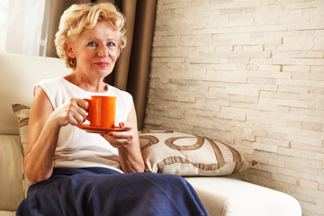 Beautiful senior woman holding cup, at home