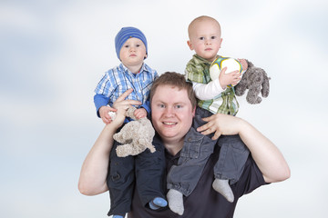 Father carrying his twin children on shoulders