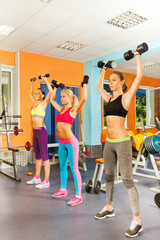 Three girls exercising with dumbbells