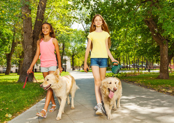 Two teenage girls walking with dogs in park