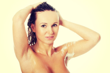 Young attractive woman taking shower and shampooing her hair.