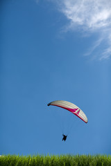 Paragliding white clouds in the blue sky Grass background