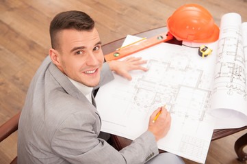 Young handsome architect engineer working on design plan