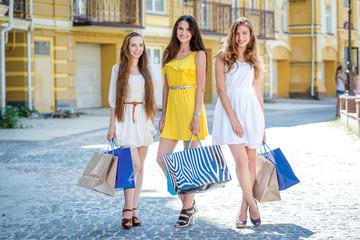Smiling girls shopaholics. Girls holding shopping bags and walk