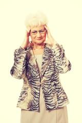 An old elegant lady is having a headache.