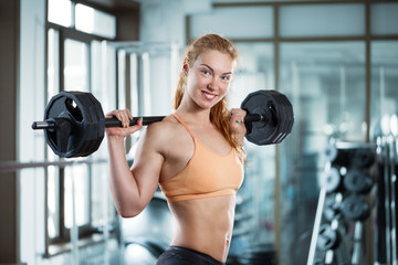 Woman in the gym with barbell