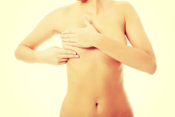 Young topless woman is examinning her breasts.
