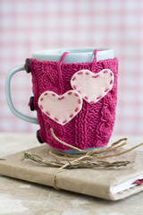 Blue cup in pink sweater with felt hearts standing on notebook