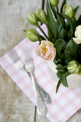 Bouquet of delicate pink tulips on the tablecloth and two forks