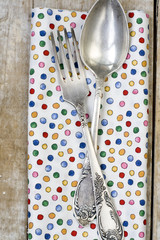 Spoon and fork lying on bright tablecloth