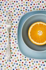 Juicy orange on blue plate for breakfast
