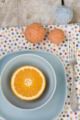Juicy orange on blue plate for breakfast and bright balls
