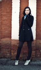Beautiful young thoughtful girl near brick wall