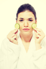 Beautiful woman in bathrobe holding slices of cucumber.
