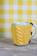 Blue cup in a yellow sweater on a yellow background
